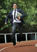 Businessman in suit and necktie carrying folder running desperate in stress on athletic track — ストック写真