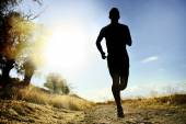 Front silhouette young sport man running cross country workout at summer sunset — Stock Photo