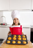 Proud female child presenting her self made muffin cakes learning baking wearing red apron and cook hat smiling happy — Stock Photo