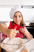 Happy little girl learning baking mixing flour in bowl wearing red apron and cook hat smiling satisfied — Stock Photo