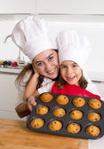 Happy mother with daughter wearing apron and cook hat presenting muffin set baking together at home kitchen — Stock Photo