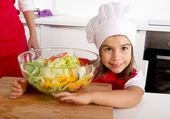 Sweet little girl  at home kitchen in red apron and cook hat holding vegetable salad bowl — Stock Photo