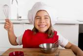 Sweet little girl in red apron and cook hat playing chef learning cooking at home kitchen — Stock Photo