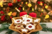Biscuits and candles under christmas tree — Stock Photo