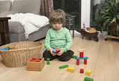 Boy playing with wooden blocks — Photo