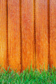 Lath wooden fence and green grass — Stock Photo