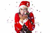Woman dressed in santa claus blowing confetti — Stock Photo