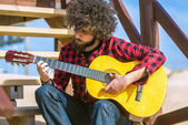 Guitarist with plaid shirt and afro hair — Stock Photo