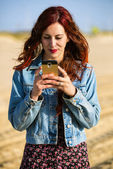 Young redhead woman with smartphone — Stock Photo