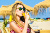 Woman drinking a orange drink at a beach bar — Stock Photo