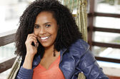Brunette woman on hammock talking on mobile phone — Stock Photo