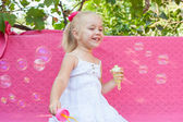 Happy little girl with soap bubbles — Stock Photo