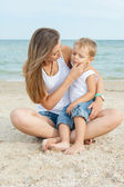 Mother and her son having fun on the beach — Stock Photo