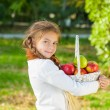 Little girl holding a basket of apples — Stock Photo #57620591