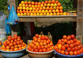 Fruit at open air market, red ripe persimmon — Stock Photo