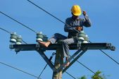 Asian electrician climb high, work on electric pole — Stock Photo