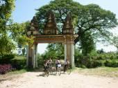 Group Asian kids, riding bike, Khmer village gate — Stock Photo