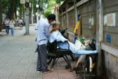 Vietnamese open air barber shop on pavement — Stock Photo