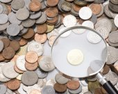 Magnifier and coins — Stock Photo