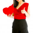 Young woman holding heart shape cushion and showing thumbs up sign — Stock Photo #57706757
