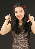 Asian young woman dressed up as an devil pointing towards camera with both hands — Stockfoto