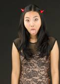Asian young woman dressed up as an devil sticking out her tongue — Stock Photo