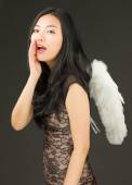 Asian young woman dressed up as an angel whispering — ストック写真