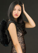 Asian young woman dressed up as a black angel scratching her head — Stock Photo