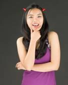 Lado de demônio de uma jovem mulher asiática em pé com mão no queixo e sorrindo — Fotografia Stock