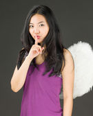 Angel side of a young Asian woman standing with finger on lips asking for silence — Stock Photo