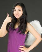 Angel side of a young Asian woman showing thumbs up sign and smiling — Stock Photo