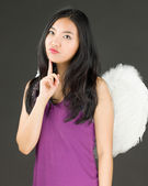 Angel side of a young Asian woman thinking with finger on chin — Stock Photo