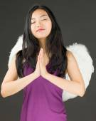 Angel side of a young Asian woman standing in prayer position — Stock Photo