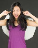 Angel side of a young Asian woman shouting in frustration with fingers in ears — Stock Photo