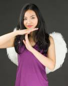 Angel side of a young Asian woman making time out signal with hands and smiling — Stock Photo