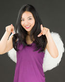 Angel side of a young Asian woman pointing with both hands and smiling — Stock Photo