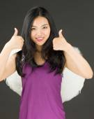 Angel side of a young Asian woman showing thumbs up sign with both hands and smiling — Stock Photo