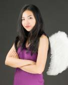 Angel side of a young Asian woman standing with her arms crossed and looking confident — Stock Photo