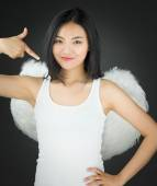 Asian young woman dressed up as an angel pointing herself with hand on hip — Stock Photo