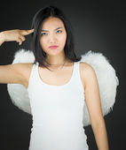 Disappointed Asian young woman dressed up as an angel shooting herself in head — Stock Photo