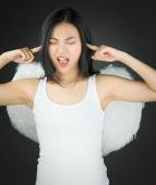 Frustrated Asian young woman dressed up as an angel with fingers in ears — Stock Photo