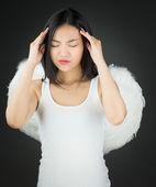 Stressed Asian young woman dressed up as an angel suffering from headache — Stock Photo