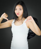 Upset Asian young woman dressed up as an angel showing thumbs down sign from both hands — Stock Photo