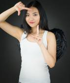 Asian young woman dressed up as an angel making frame with fingers — Stock Photo