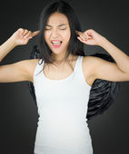 Asian young woman dressed up as an angel shouting in frustration with fingers in ears — Stock Photo