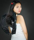 Rear view of a Upset Asian young woman dressed up as an devil turning back — Stock Photo