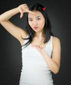 Asian young woman in devil horns and making frame with fingers — Stock Photo