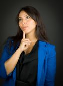 Thoughtful young businesswoman looking up with her finger on chin — Stock Photo