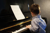 Profile of a little boy learning piano — Stock Photo