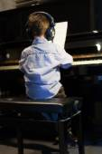 Rear view of a little boy learning piano — Stock Photo